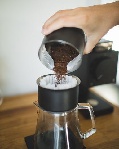 Pouring coffee grinds into Stagg [X] Dripper