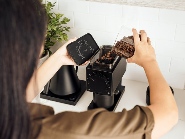 Woman pouring coffee from Atmos Vacuum Canister in Ode Brew Grinder