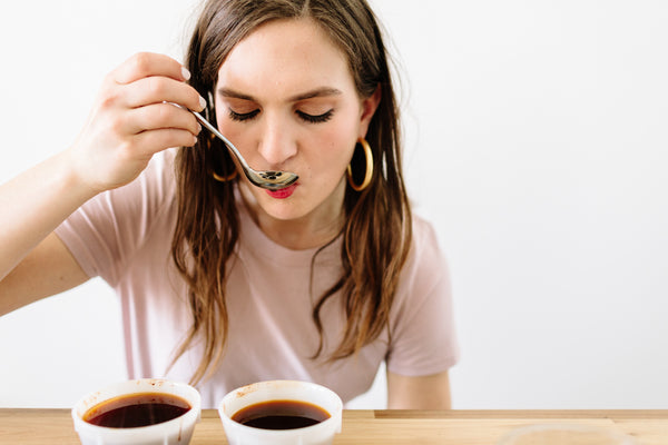 Woman tasting cupped coffee