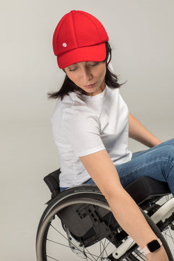 Model wearing red Baseball cap with chin strap by Ribcap
