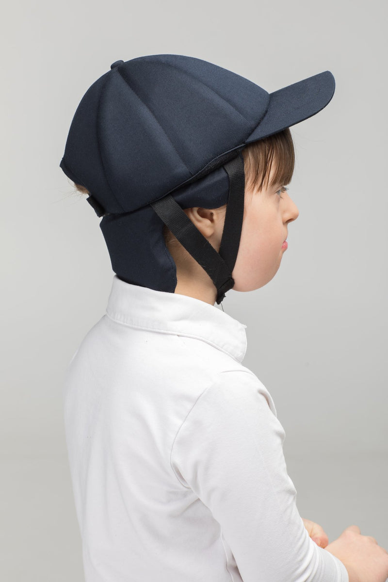 Model wearing extra protective soft helmet for kids with chin strap by Ribcap