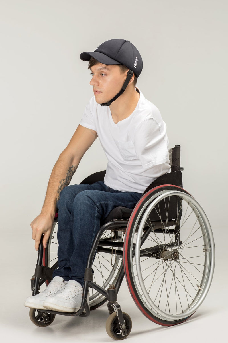 Man in wheelchair wearing a soft helmet hat, designed like a baseball cap for seizures by Ribcap