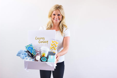 Georgia the Caring Canary founder holding a care package gift hamper