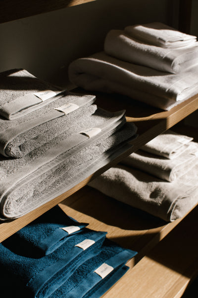 folded organic cotton towels, made in Turkey, in blue, white, grey, and beige, on shelf.