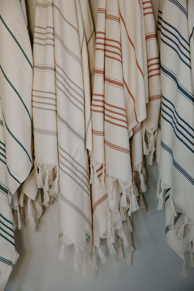 hanging organic cotton Turkish towels striped in blue, green, red, and grey