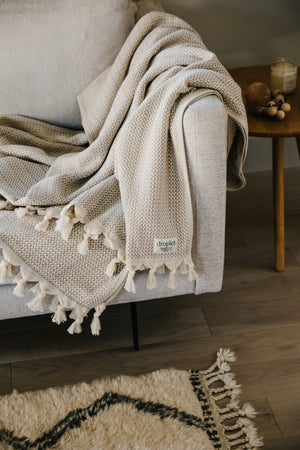 beige organic cotton blanket with tassels on sofa