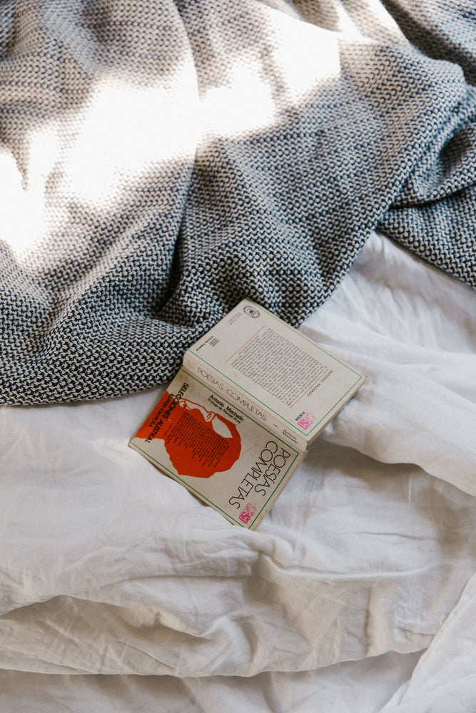 blue organic cotton blanket on bed with book