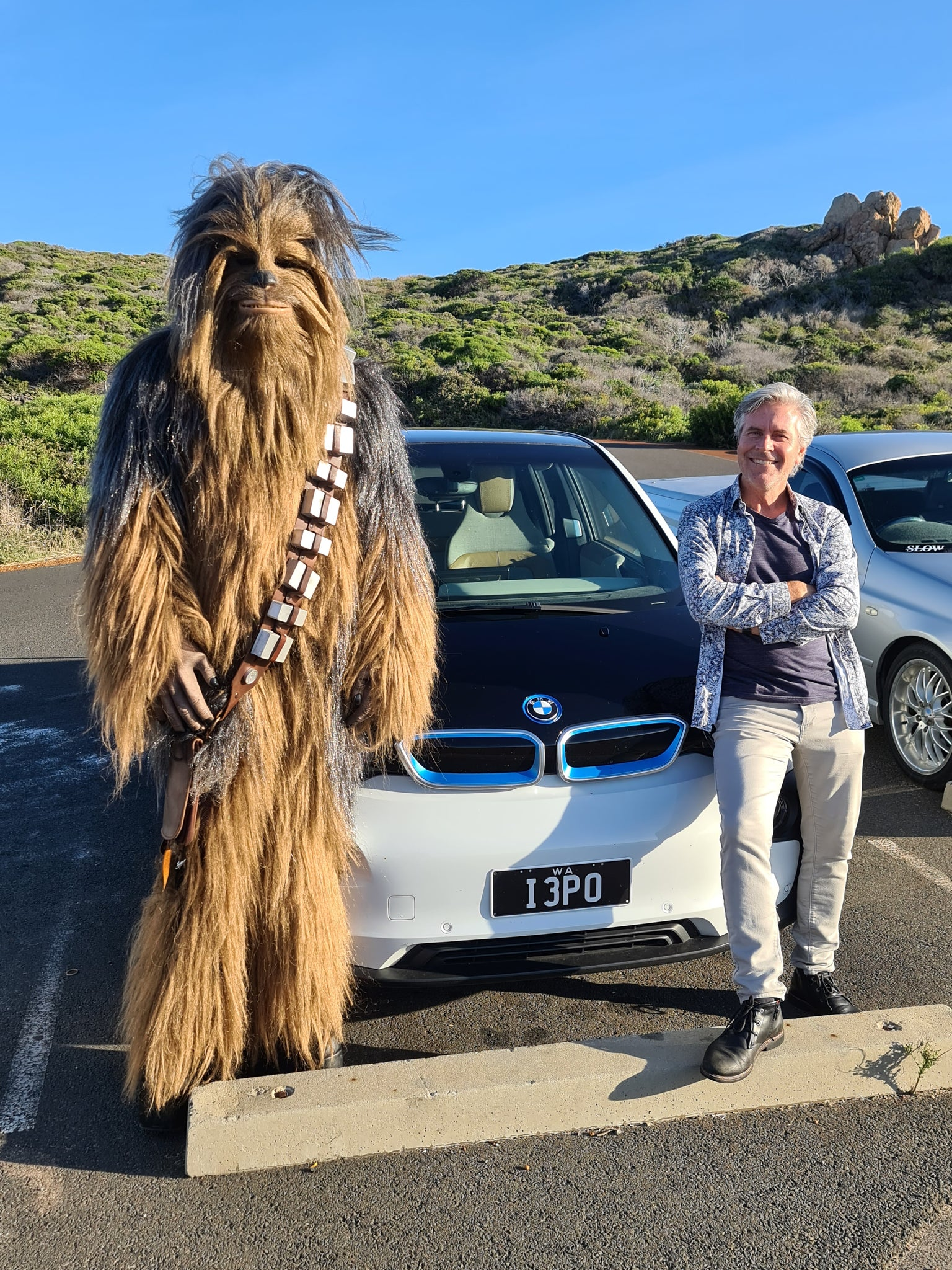 Christian Fletcher and Chewbacca standing in front of a BMW i3 at Sugarloaf Rock in Western Australia