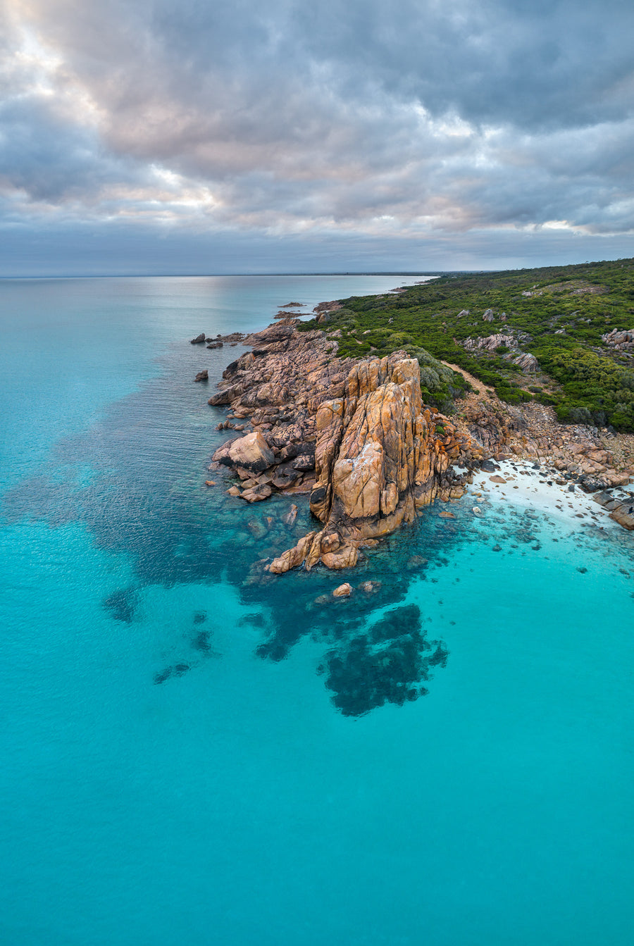 Aerial photograph of Castle Rock, Dunsborough, Western Australia.  The turquoise waters of Geographe Bay with Castle Rock in the foreground looking to Dunsborough in the background.  Morning sunrise with clouds over the calm blue water.