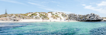 Summer time on a small island off Perth, Western Australia.  A photograph taken from the water looking back to the beach where people are swimming, sunbathing and walking on the limestone cliffs.