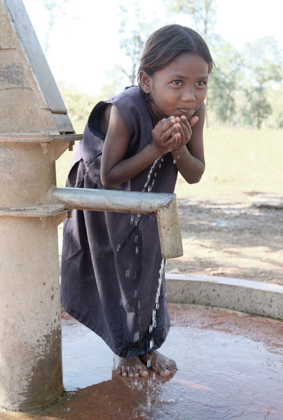 Girl in India drinks from water pump