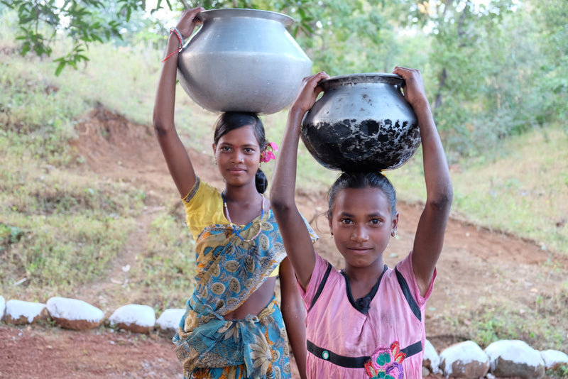 Young girls in India carrying water a short distance, thanks to FRANK Water