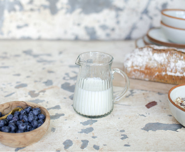 Bread, jug of milk and bowl of blueberries