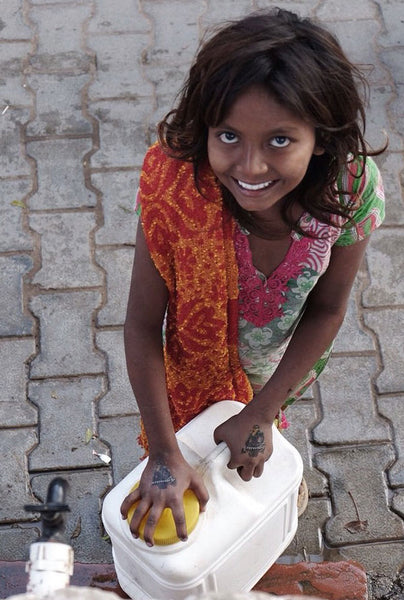Girl in India with water can smiling