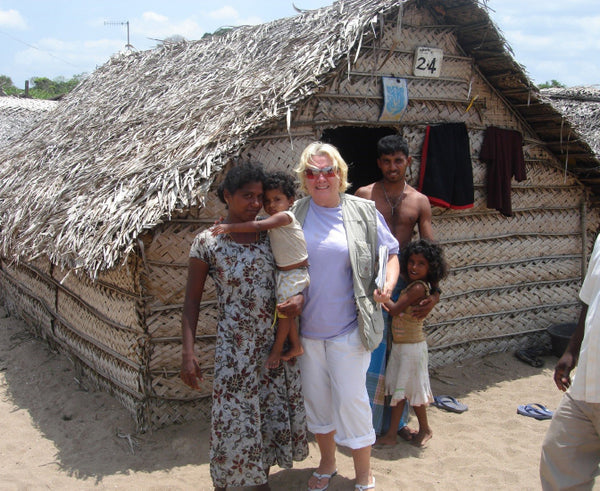 Indian family and Joy outside a traditional hut