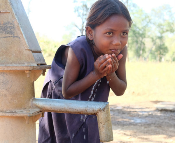 Young Indian girl drinking water with hands