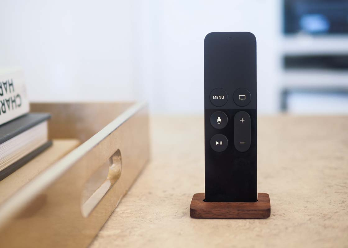 a close-up of the Apple TV remote on a stone coffee table being held upright by the stand.