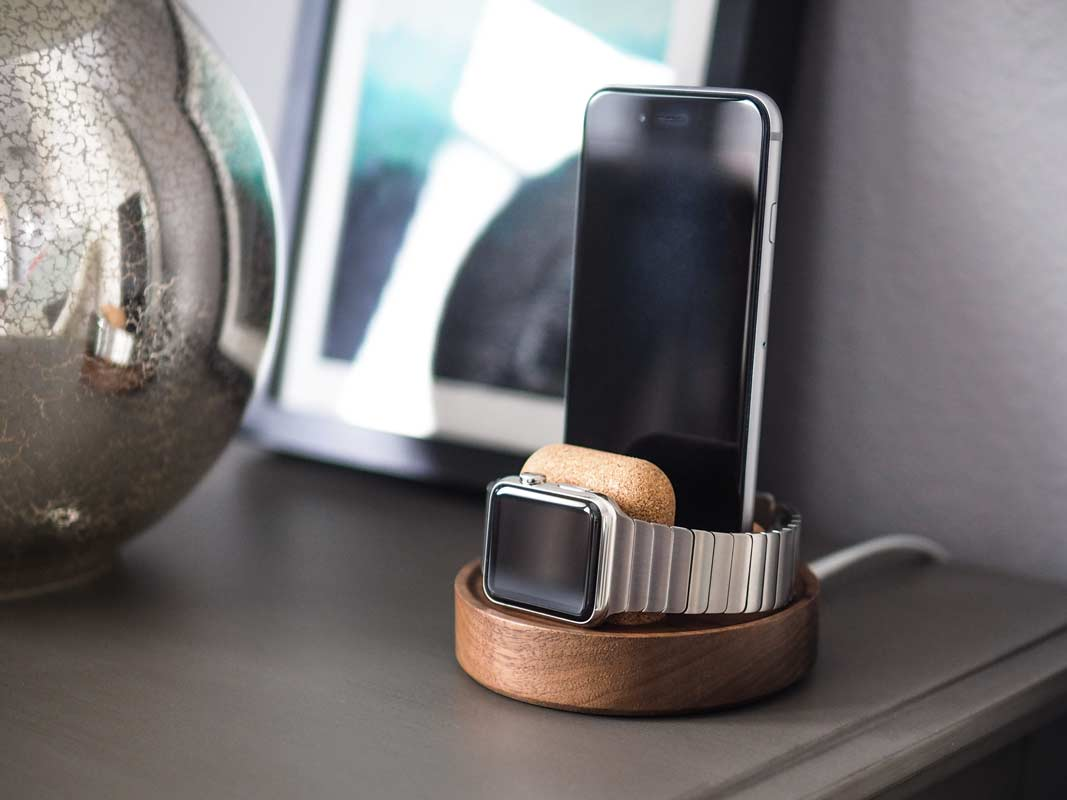 an Apple Watch and phone changing standing up on one dock.