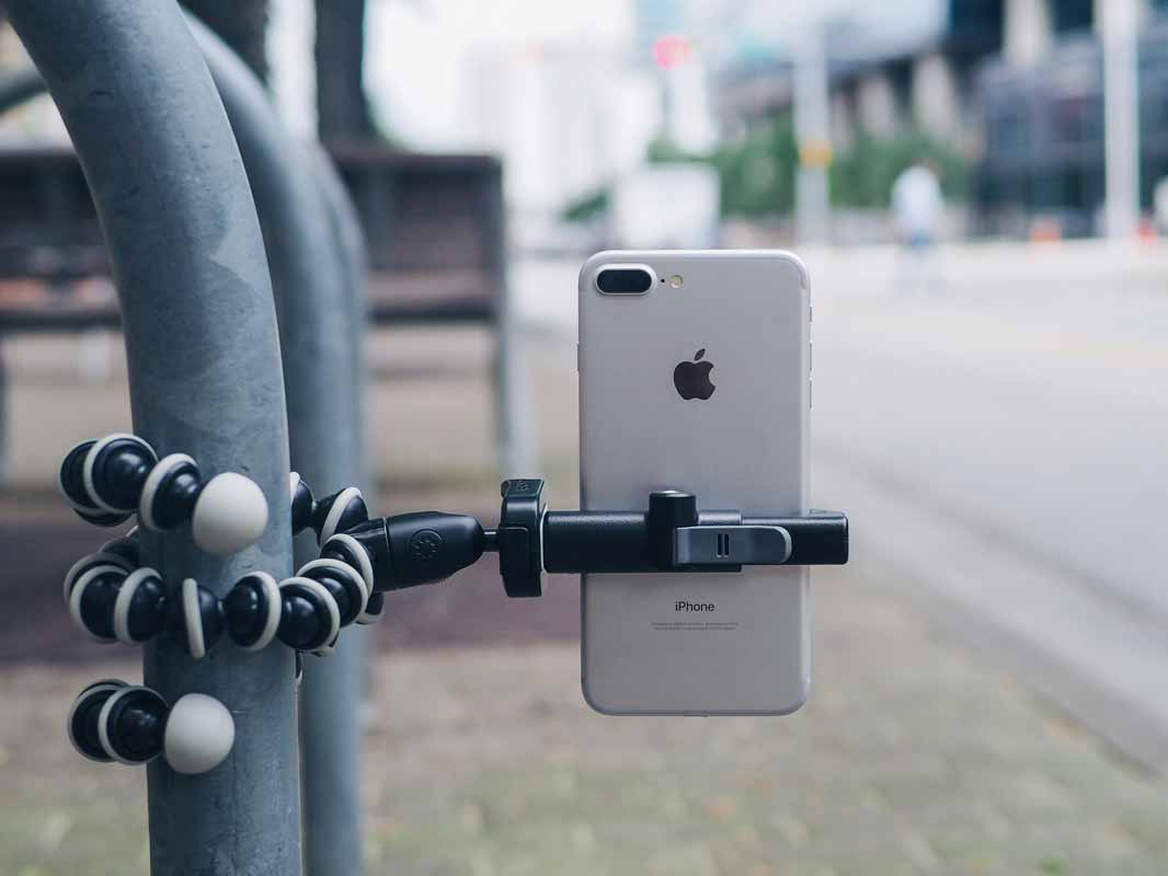 the glif attached to a vertical pole via a tripod holding a phone vertically.