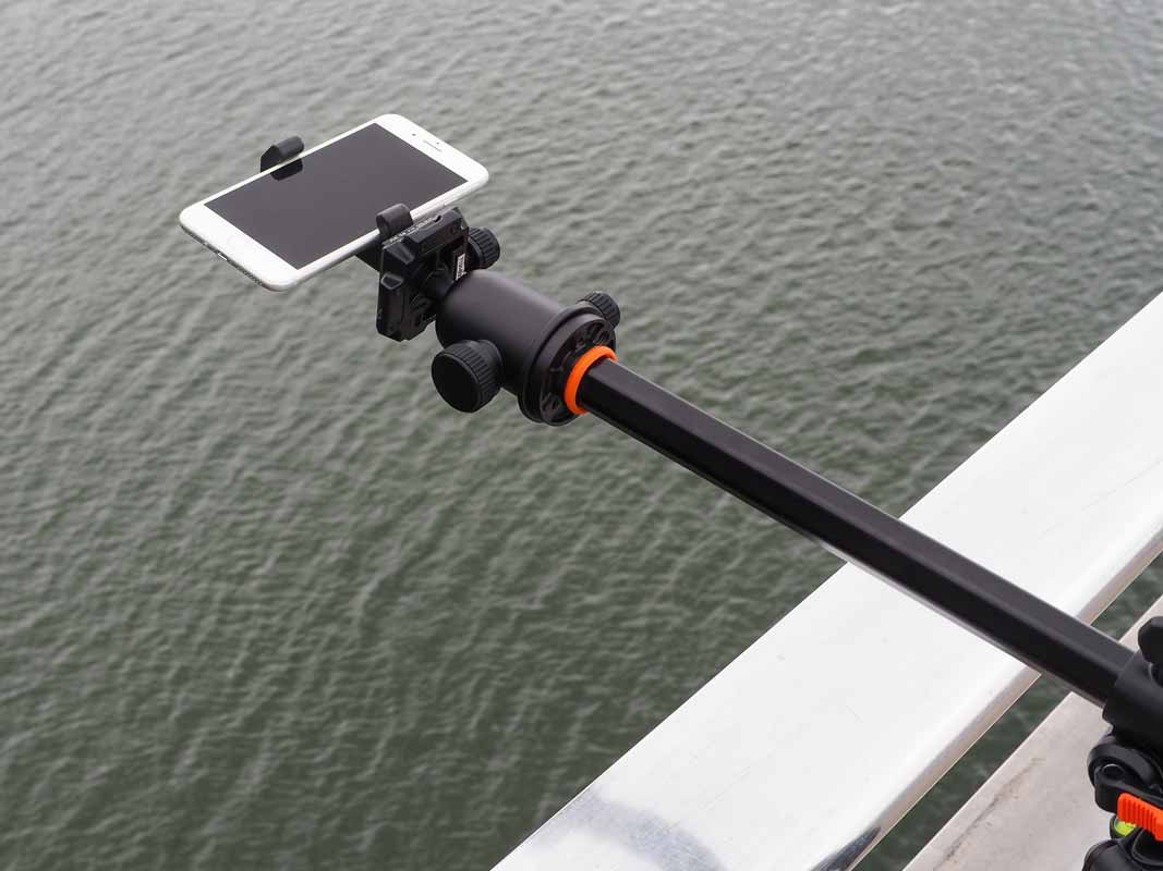 the glif holding a phone over water via a tripod arm.