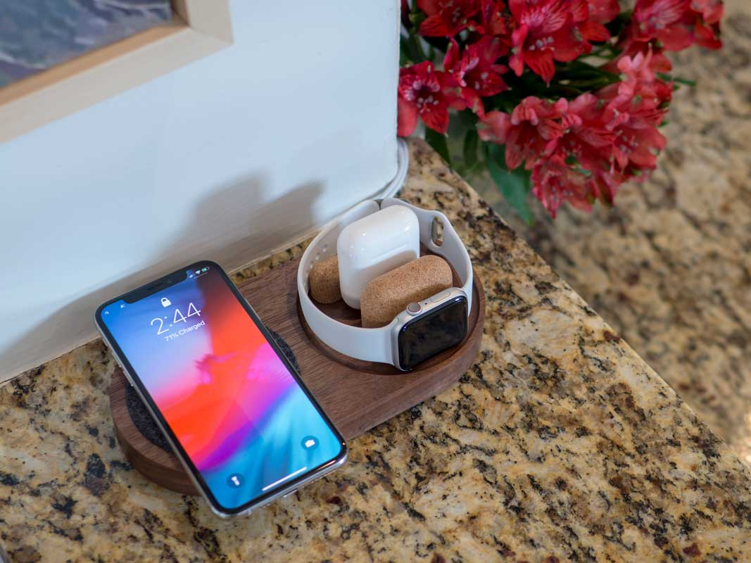 a material dock with a phone charging via qi, an Airpods case charging via cable, and an Apple Watch charing on it's side.