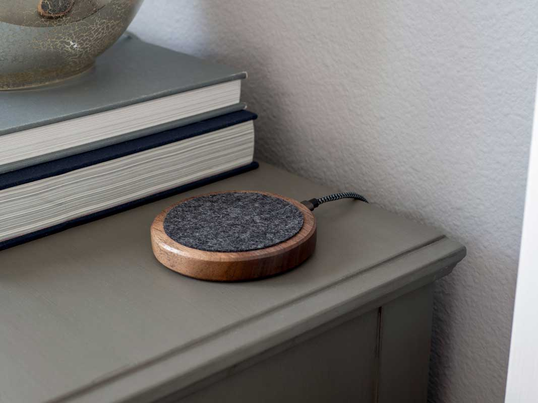 the qi-only material dock sitting on a night stand.