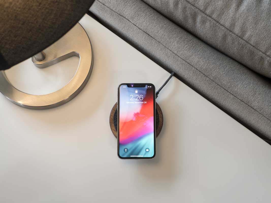 a phone laying on a qi charging pad in a living room.