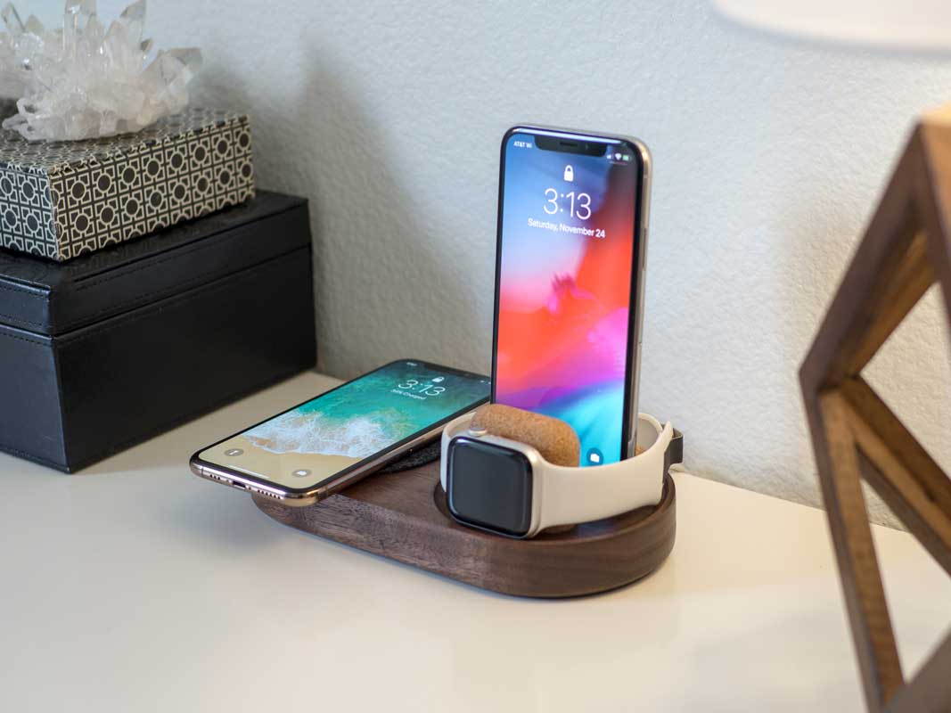 a phone laying on a qi charging pad, a phone standing upright charging via a lightning cable, and an Apple Watch charging on it's side, all on one dock.