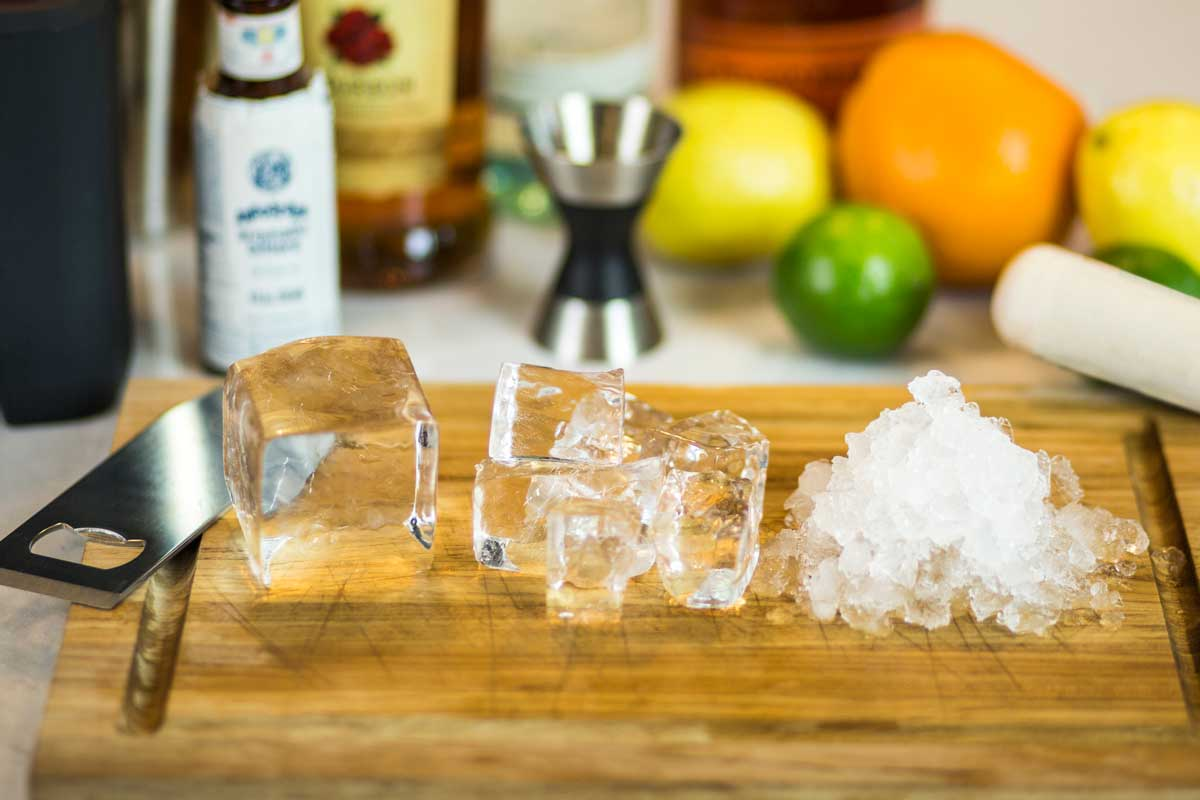 three types of ice on a cutting board that can be made with the Neat Ice Kit: large block, cubes and crushed.