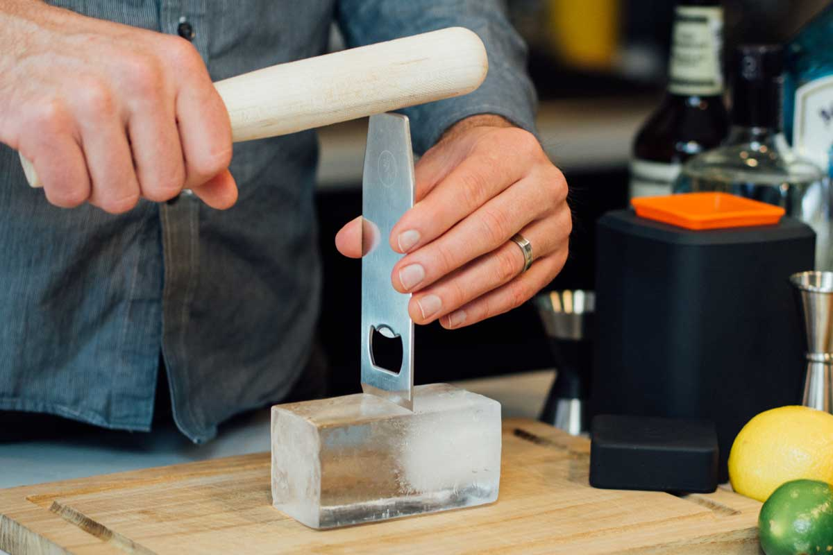a person using the muddler to hit the chisel into an ice brick to split it.
