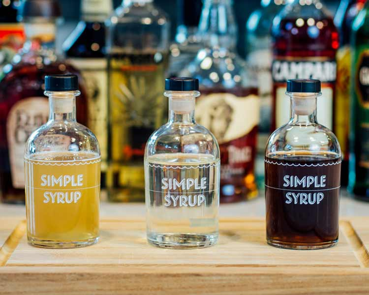 three different types of simple syrup in bottles on a cutting board.