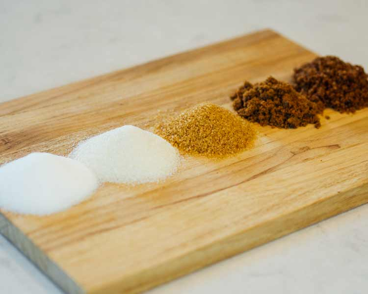 piles of different types of sugars on a cutting board.