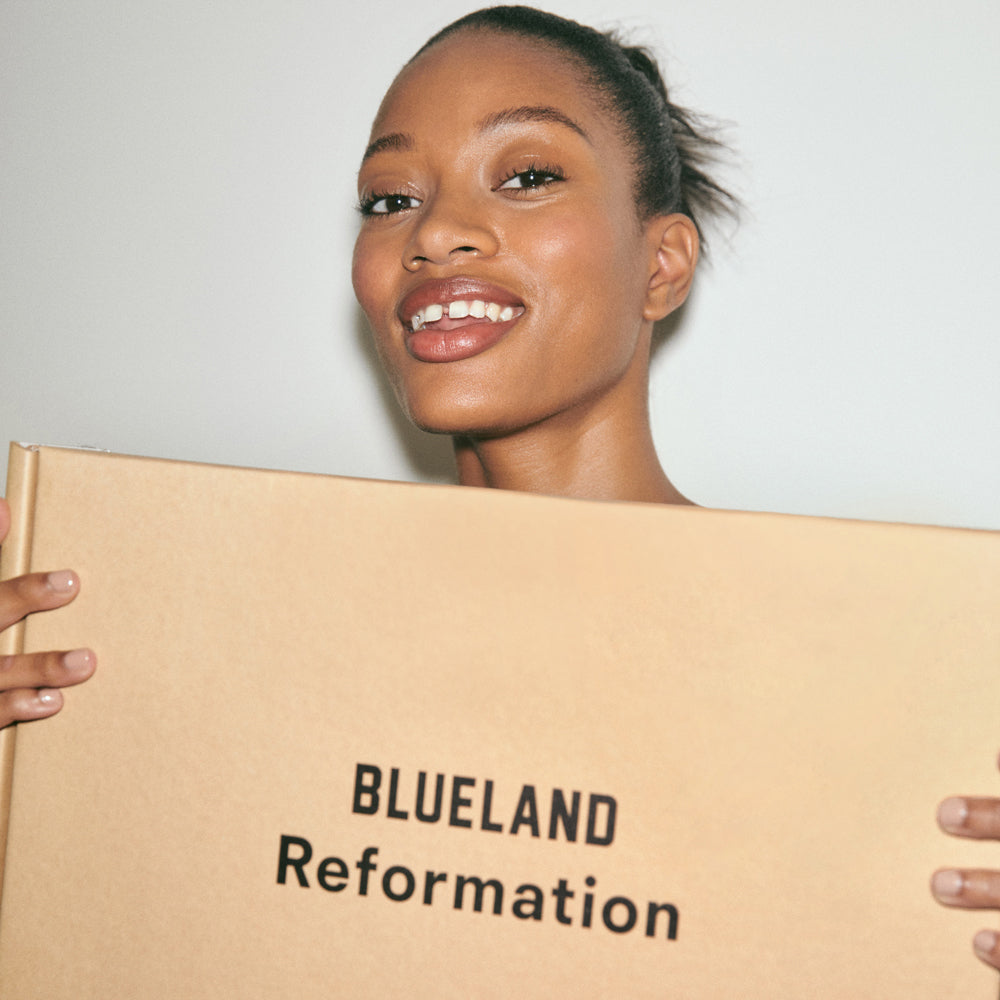 Model against white background holding the corrugate box for the Blueland x Reformation Routine Clean Kit