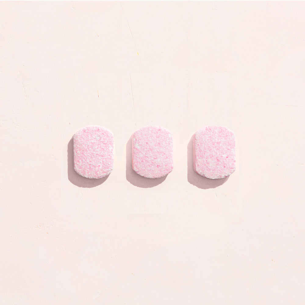 Three bathroom cleaning tablets on pink background