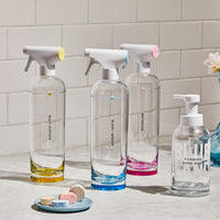 Clean Essentials Kit with one Multi-Surface Forever Bottle, One Glass + Mirror Forever Bottle and one Bathroom Forever Bottle and a glass Foaming Hand Soap bottle with unwrapped tablets on a blue plate all placed on white marble counter