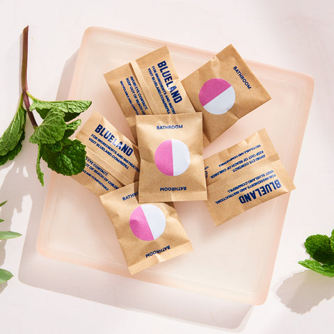 Bathroom cleaner refill packs - scented, on a cutting board with fresh organic herbs
