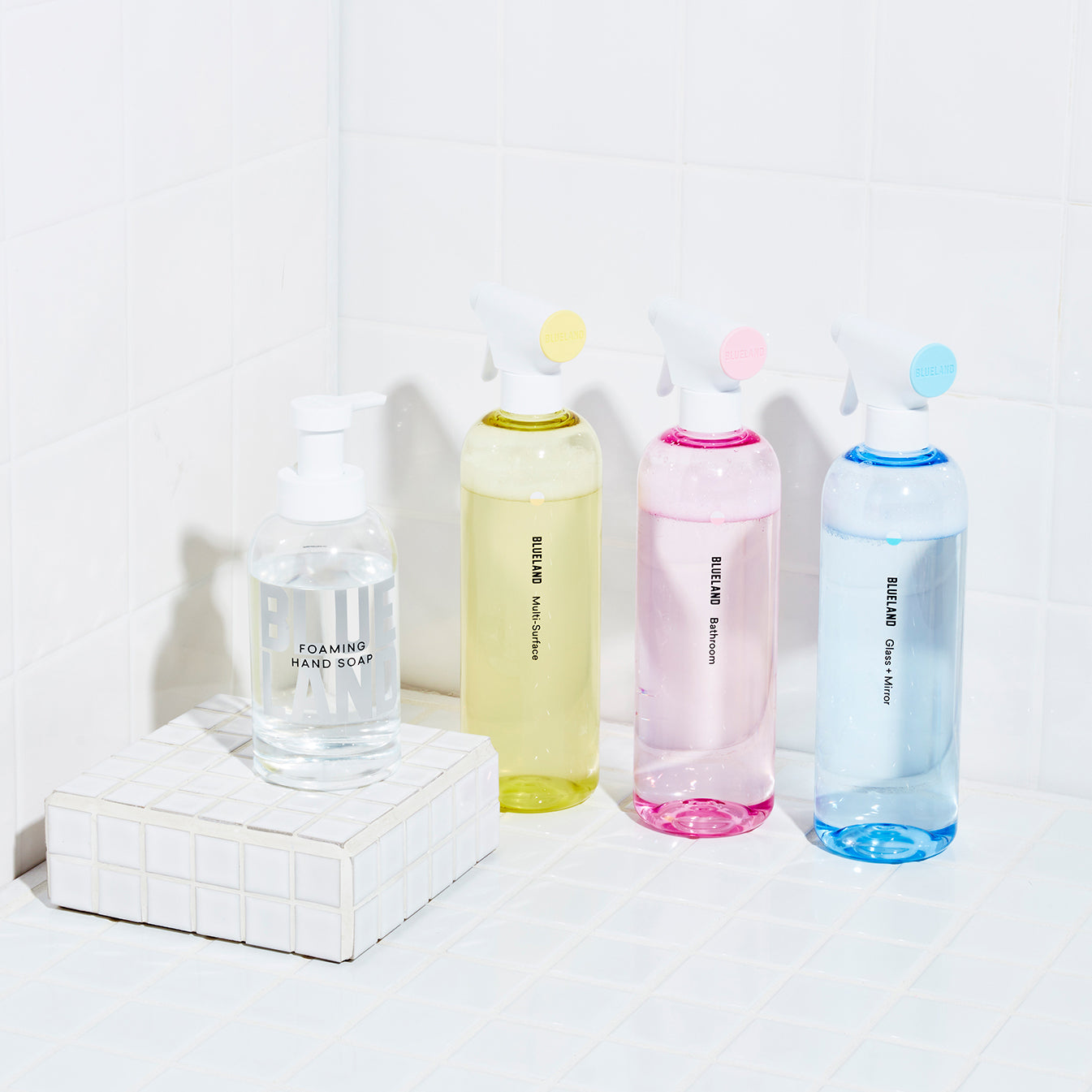 Clean Essentials Kit with one Multi-Surface Forever Bottle, One Glass + Mirror Forever Bottle and one Bathroom Forever Bottle and a glass Foaming Hand Soap bottle all placed on a white titled counter