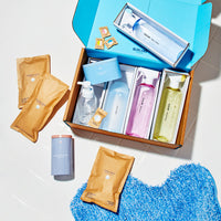 The Clean Suite: 7 Refillable, reusable cleaning vessels with tablets or powder. 3 spray Cleaners all in tritan reusable bottles with three tablets. A glass Foaming Hand Soap Bottle and foaming hand soap tablet. A silicone shaker filled with Powder Dish Soap, a refillable tin coated steel container with dishwasher tablets and a tin coated steel container with laundry tablets laid out in and around our compostable cardboard packaging.