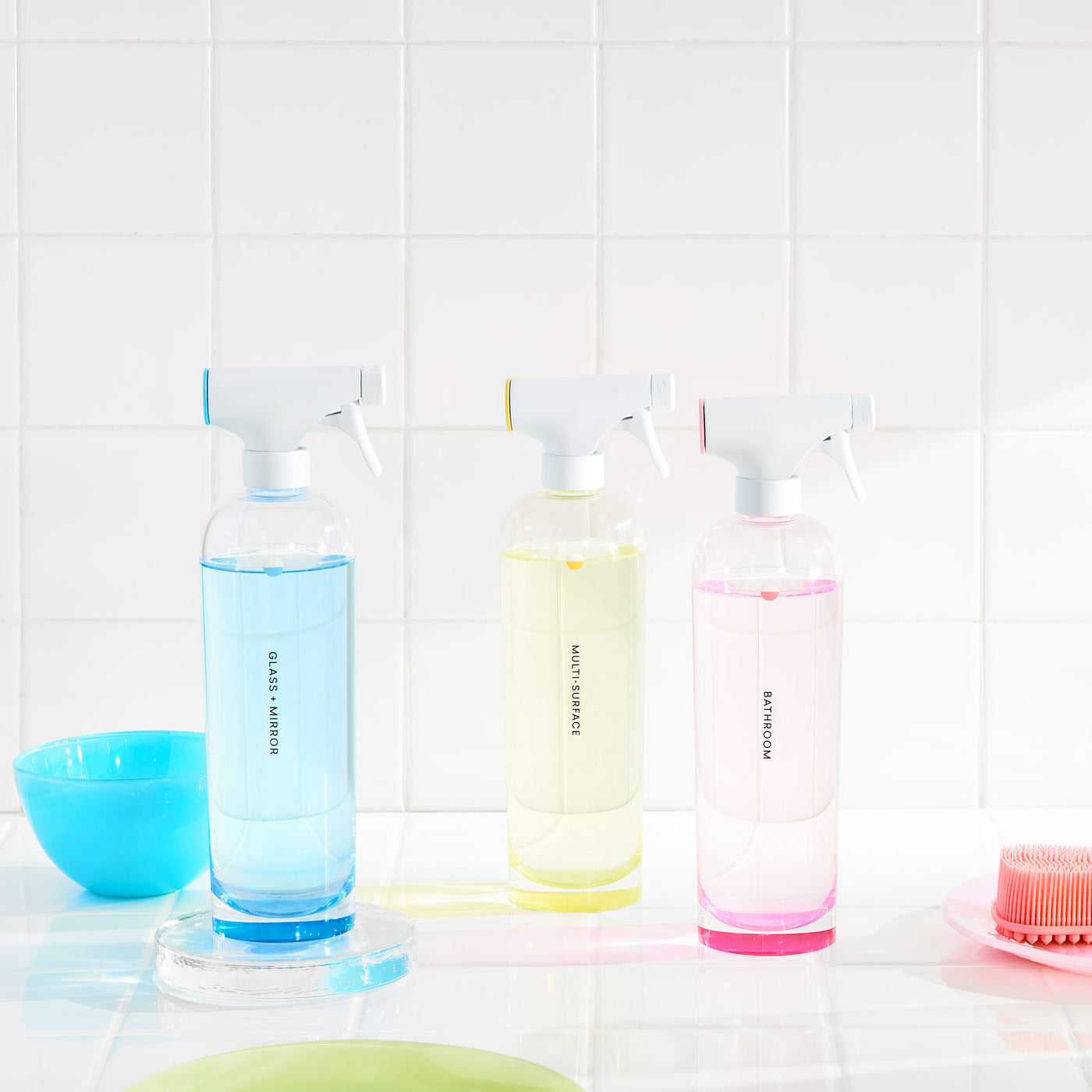 Non-toxic cleaners, scented and unscented, on display, with refillable tablets against white tile with blue bowl and pink silicone sponge
