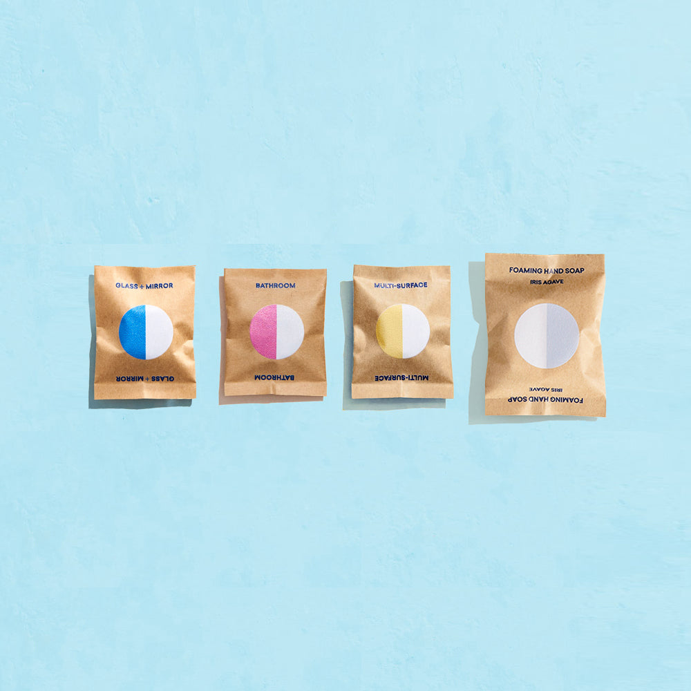 Four wrapped tablets in compostable packaging,  one Glass + Mirror tablet, one Bathroom tablet, one Multi-Surface tablet and one Foaming Hand Soap tablet agains blue background