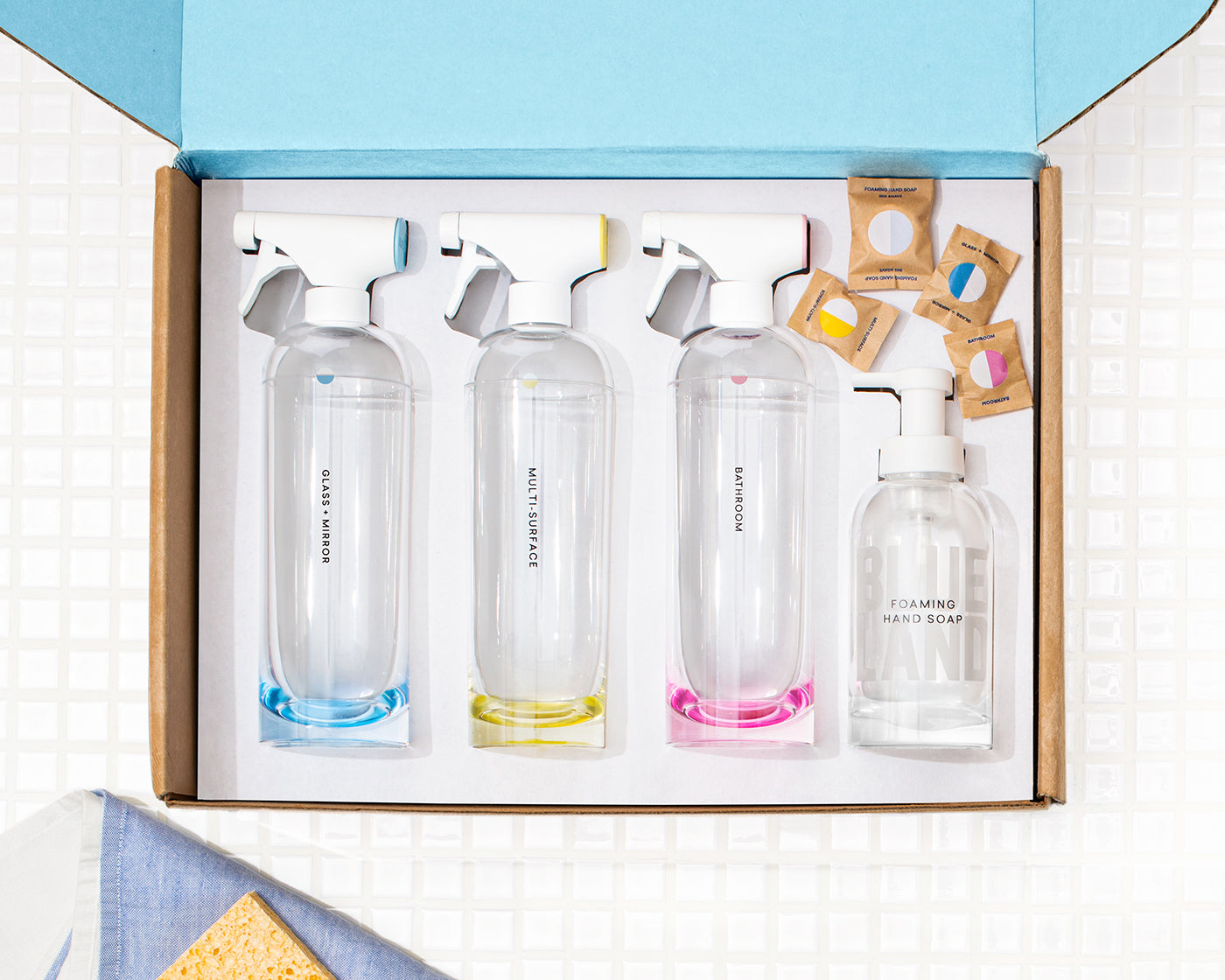 Clean Essentials Kit with one Glass + Mirror Forever Bottle, One Multi-Surface Forever Bottle, One Bathroom Cleaner Forever Bottle and one glass Foaming Hand Soap Forever bottle in the box with four cleaning tablets agains white tile background with sponge in the corner