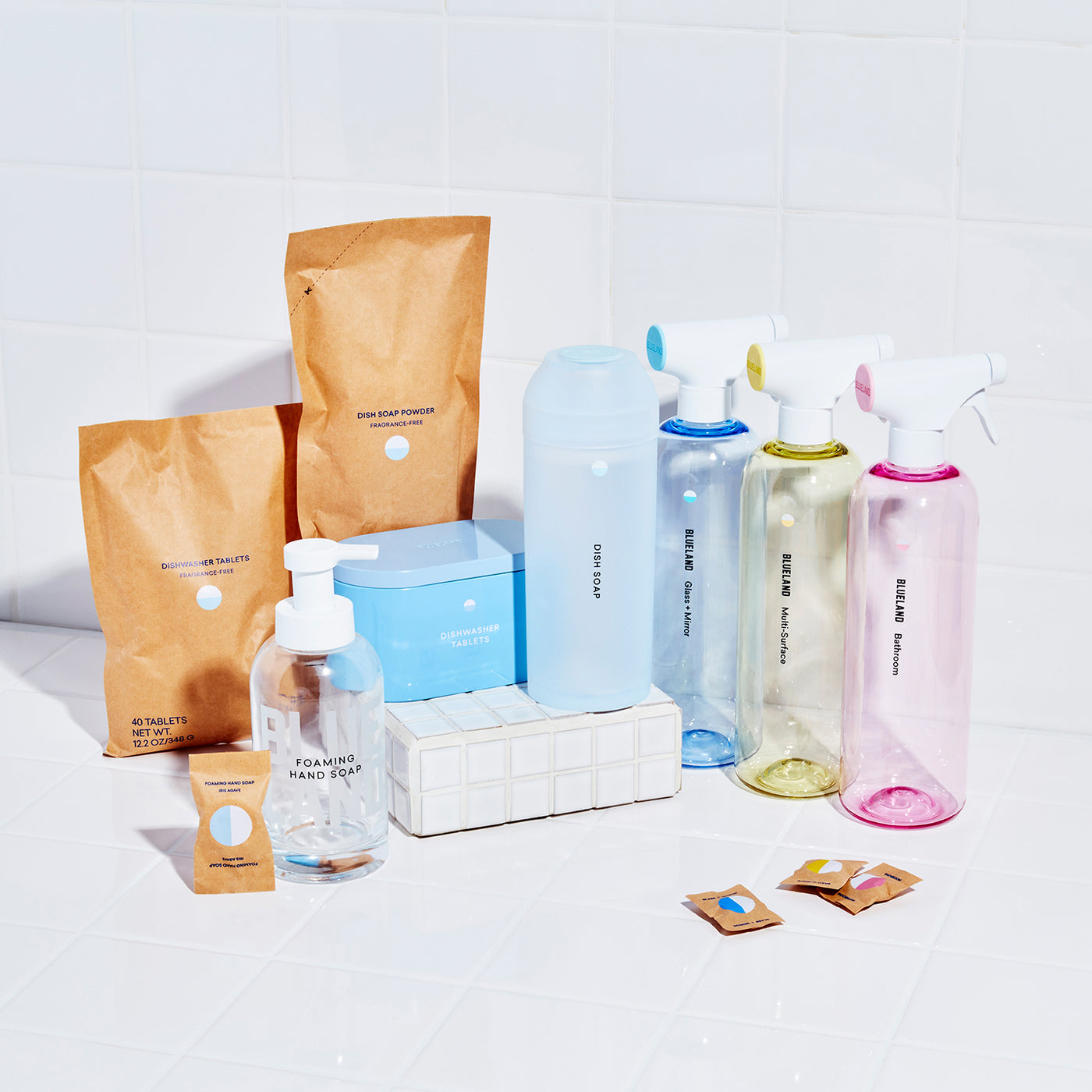 The Everyday Clean: 6 Refillable, reusable cleaning vessels with tablets or powder. 3 spray Cleaners all in tritan reusable bottles with three tablets. A glass Foaming Hand Soap Bottle and foaming hand soap tablet. A silicone shaker filled with Powder Dish Soap, a refillable steel coated tin container with dishwasher tablets. All products are on the titled surface with refill pouches for powder dish soap and dishwasher tablets in compostable packages next to their containers.