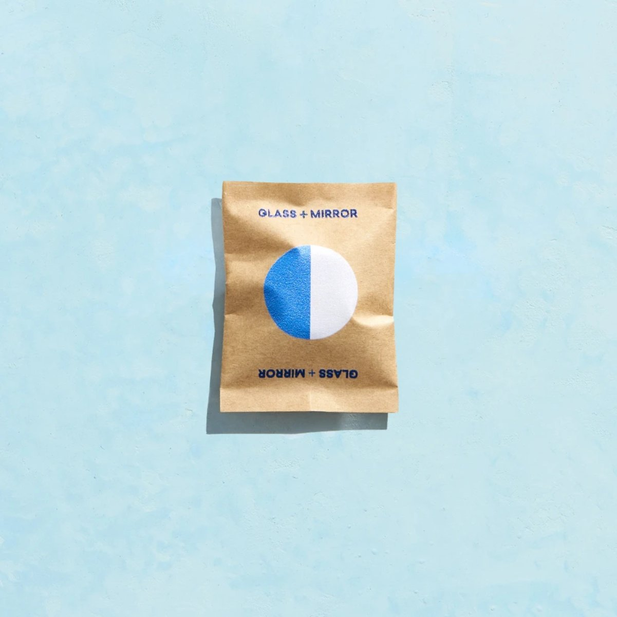 Glass + Mirror tablet wrapped in compostable brown paper on a blue background