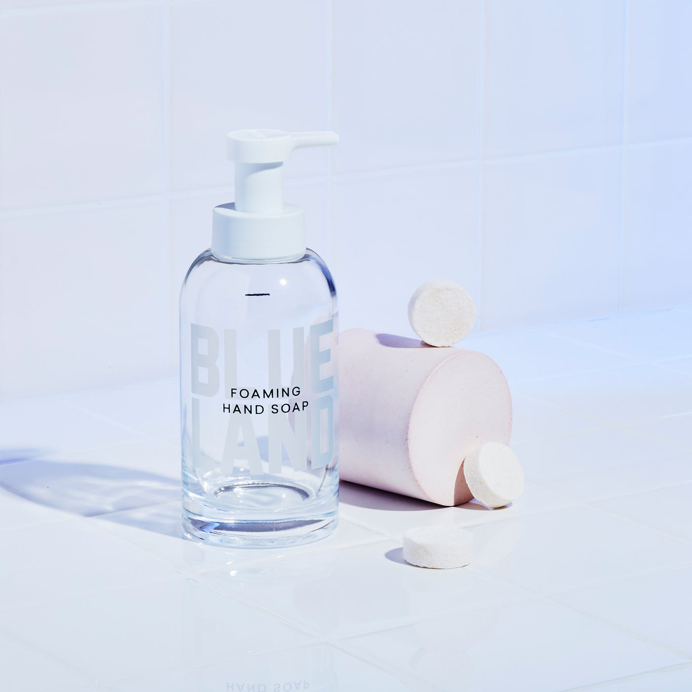 Reusable glass hand soap bottle on white tile next to 3 white hand soap tablets resting on and around pink cylinder.