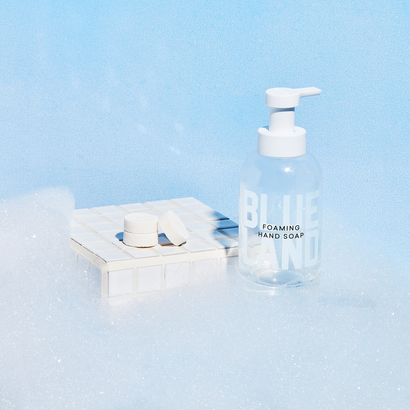 Glass hand soap bottle in suds next to white tile with 3 hand soap tablets placed on top.