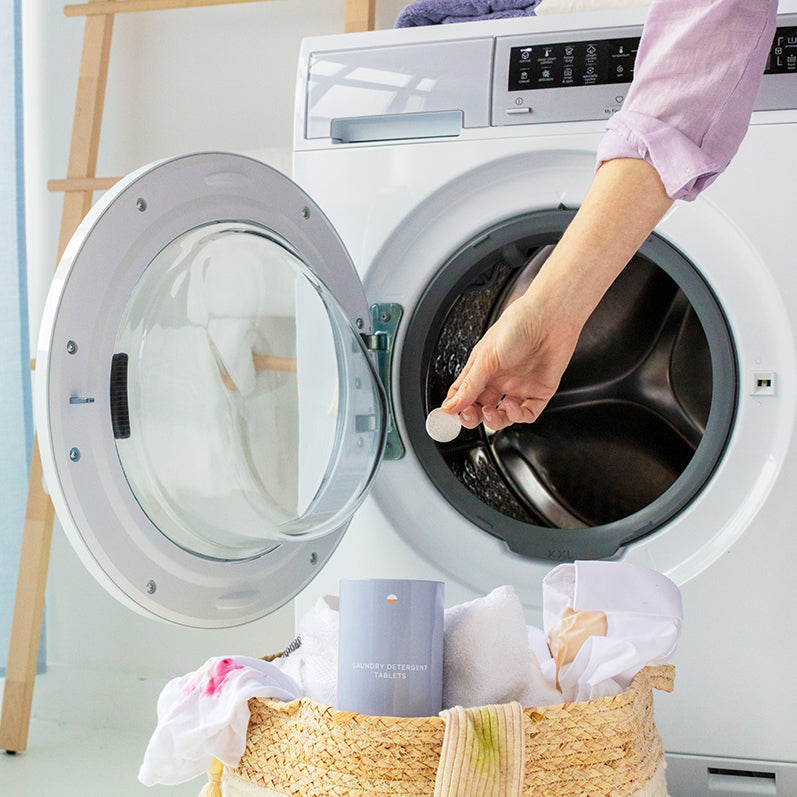 A hand holding one PVA-free laundry tablet with a tin container for laundry tablets sitting in a laundry basket of dirty clothes. An open washing machine is behind the hand.