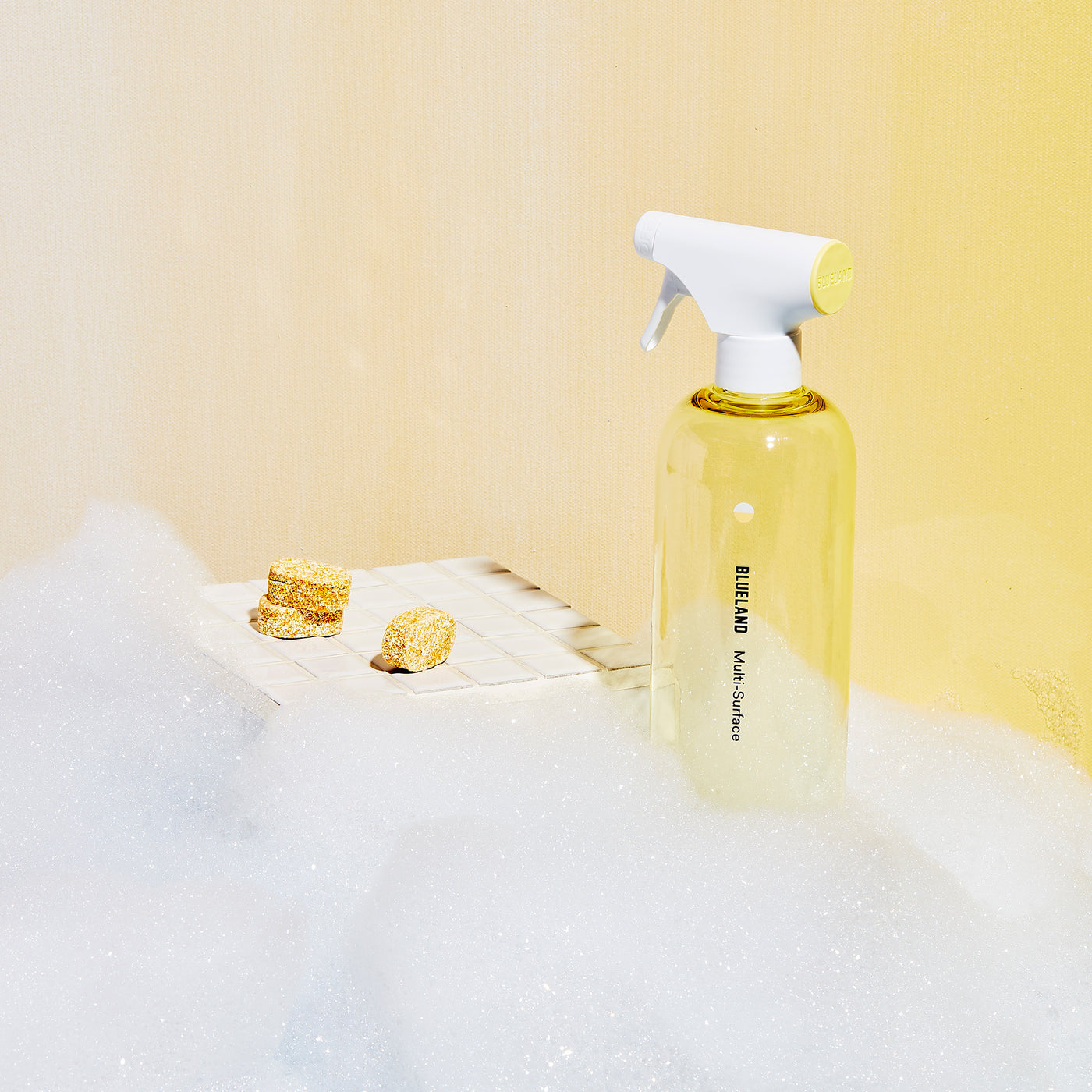 Yellow Multi-Surface Cleaner Forever Bottle with cleaning tablets laid out on white tiled surface and yellow wall behind. Foamy bubbles surround the bottles and tile.