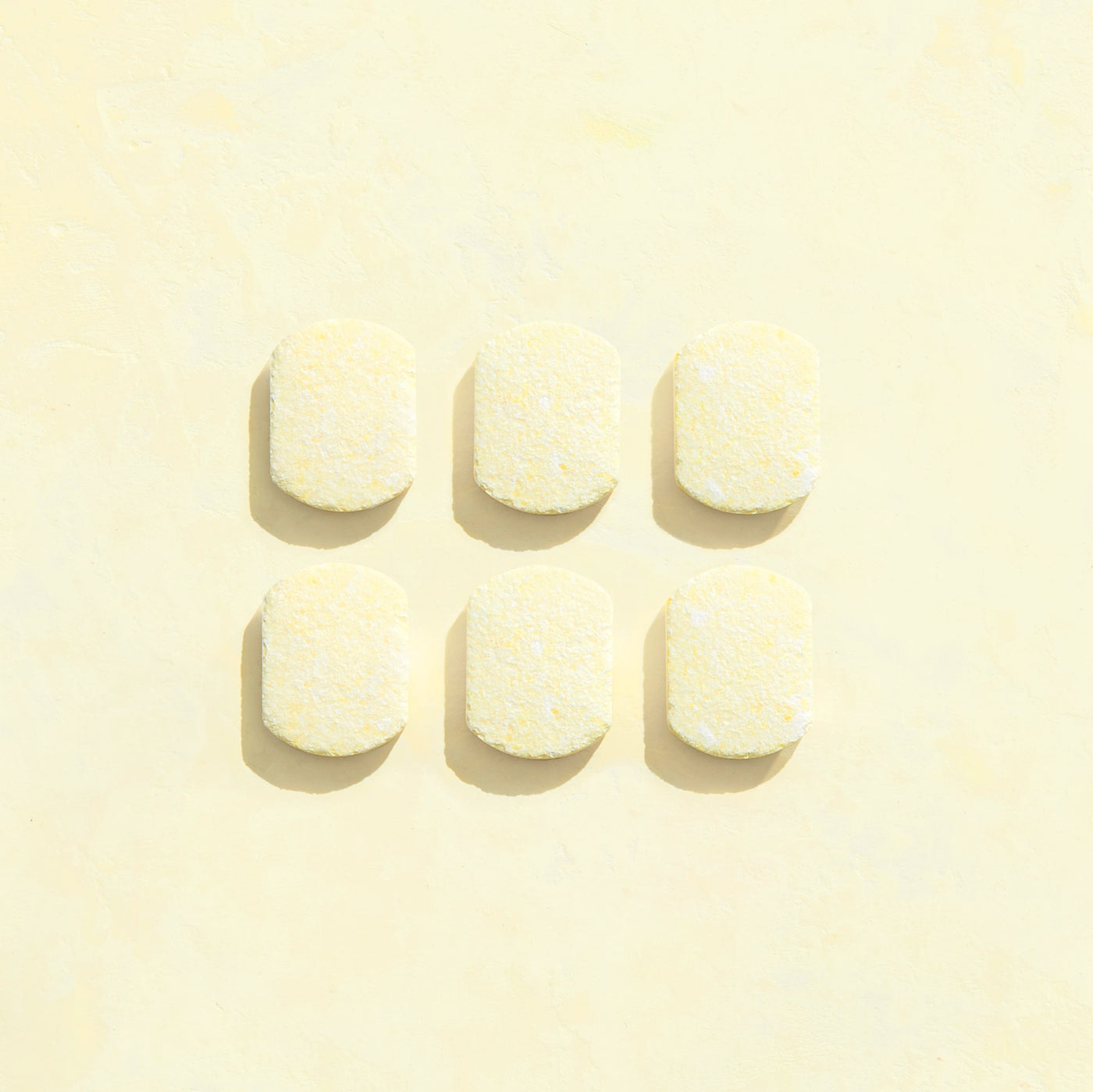 Six unwrapped lemon scented Multi-Surface Cleaner tablets