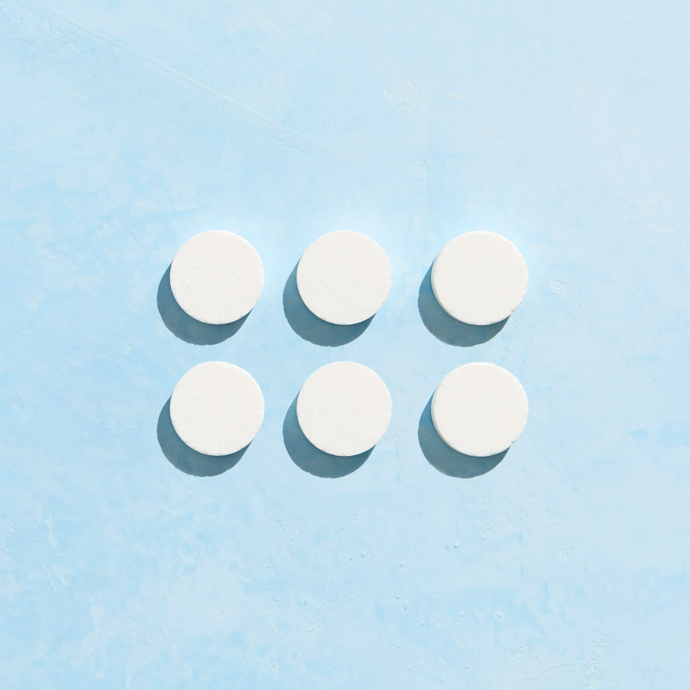 Six unwrapped Foaming Hand Soap tablets on blue background