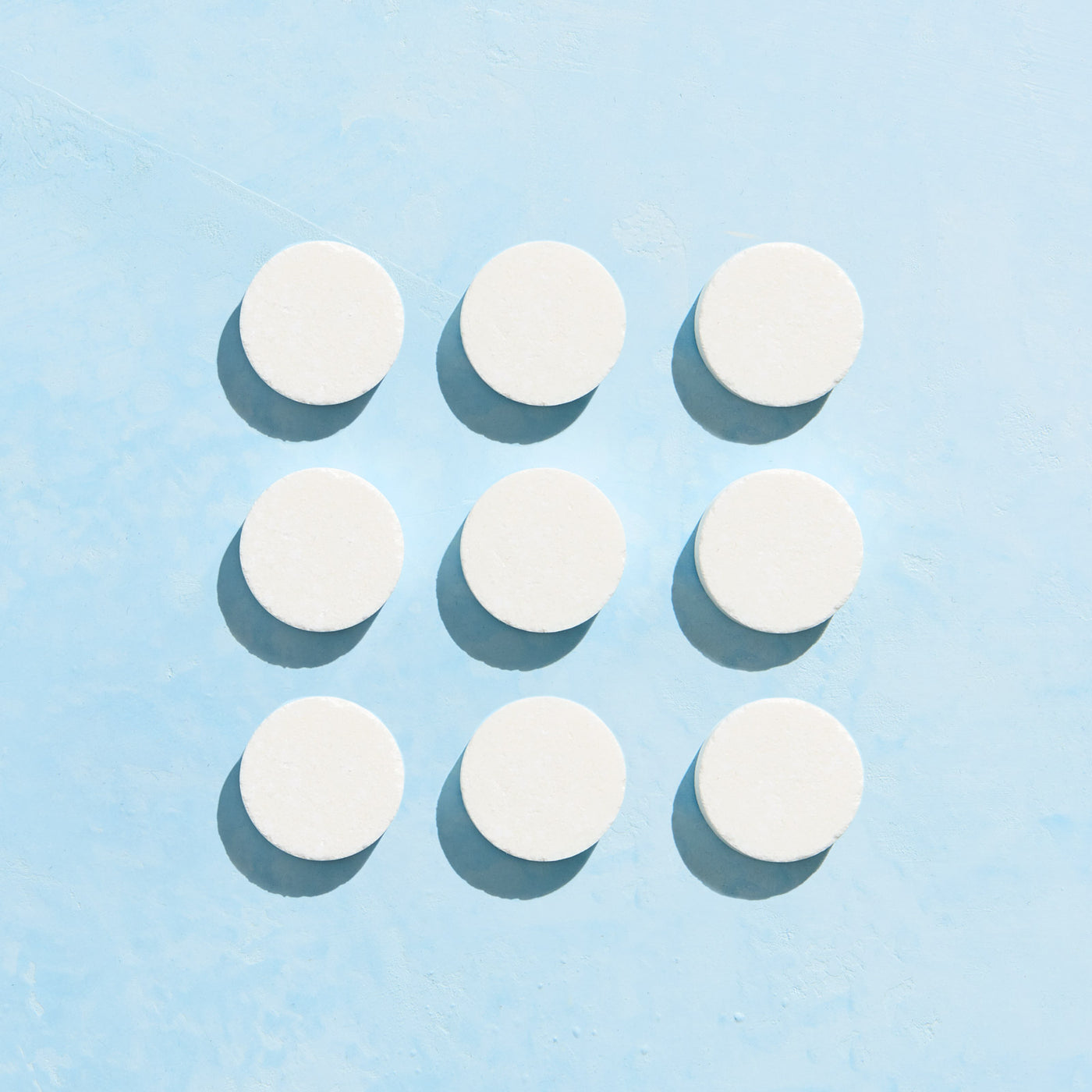 Nine unwrapped Foaming Hand Soap tablets on blue background